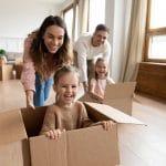 Parents heureux jouant leur enfant dans un carton de demenagement