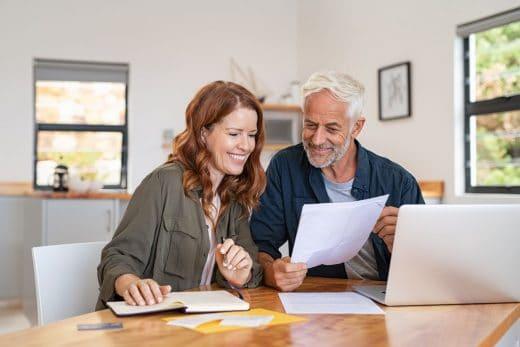 couple retraite qui regarde papier de travaux devant un ordinateur