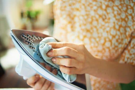 Plan rapproché sur le fer de nettoyage de femme avec le tissu